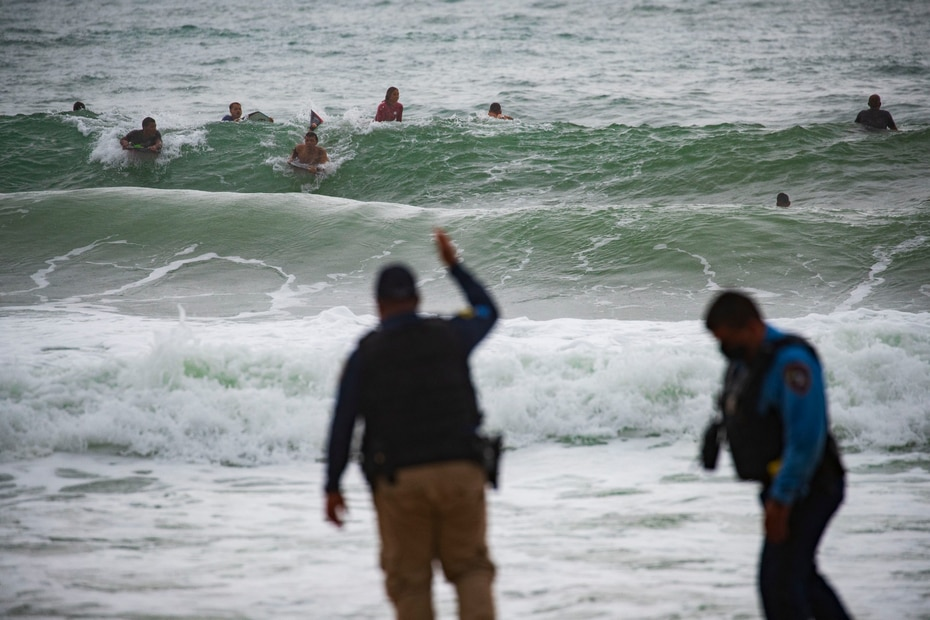 Police intervene with surfers on Aviones beach in Carolina during the passage of tropical storm Laura.