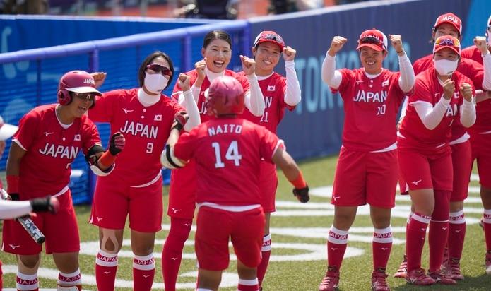 Minori Naito (14), de Japón, celebra con sus compañeras luego de anotar una carrera durante el encuentro inaugural del sóftbol femenino ante Australia.