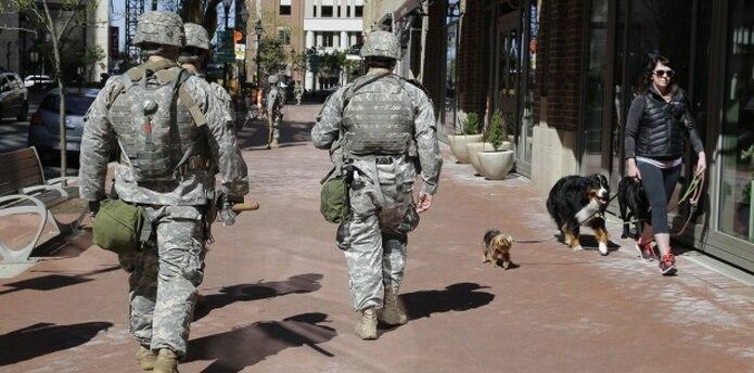 El patrullaje de la Guardia Nacional por las calles de Baltimore no impide a esta residente sacar a pasear a sus perros. (AP)