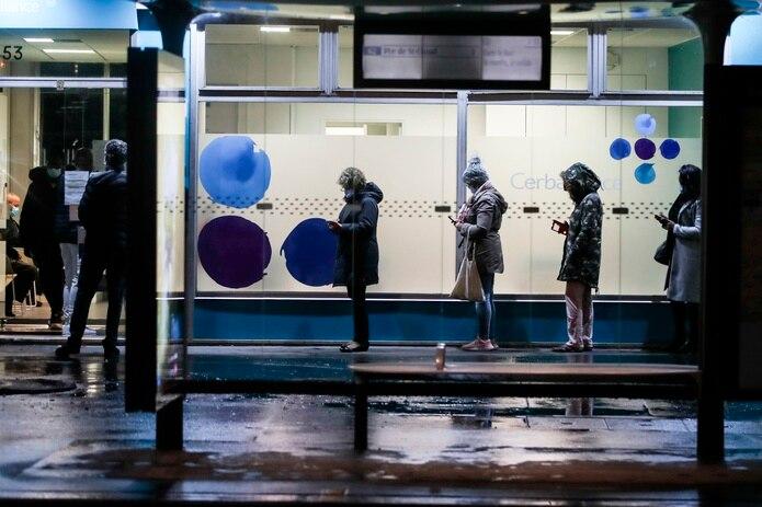 Varias personas esperan su turno en la puerta de un laboratorio de París para someterse a una prueba de coronavirus.