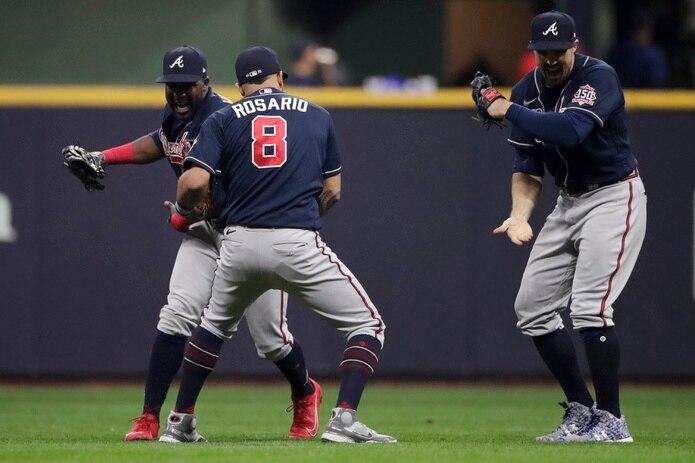 Desde la izquierda, Jorge Soler, Eddie Rosario y Adam Duvall, jardineros de los Braves de Atlanta, celebran el triunfo del sábado 3-0 sobre los Brewers de Milwaukee.
