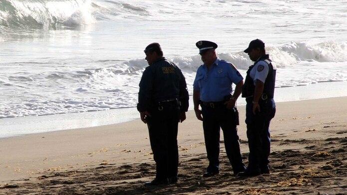 Tres agentes de la Policía investigan un ahogamiento en la playa. (GFR Media)