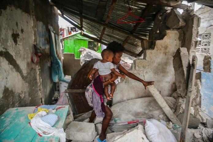 Una mujer carga a su hijo mientras camina entre los restos de su casa destruida por un sismo de 7.2 que sacudió Haití.