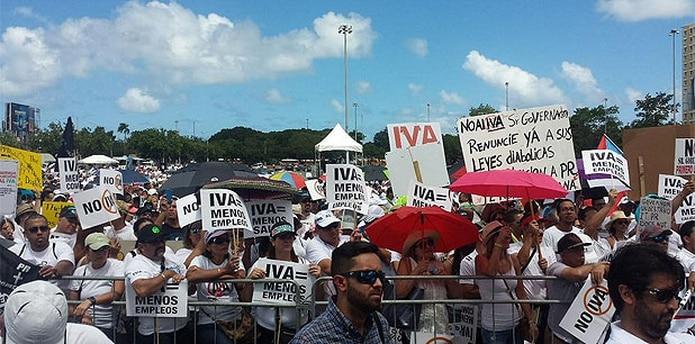 Los manifestantes se congregaron frente a una tarima colocada en el estacionamiento del complejo deportivo para escuchar consignas y mensajes en contra del IVA. (daniel.rivera@gfrmedia.com)