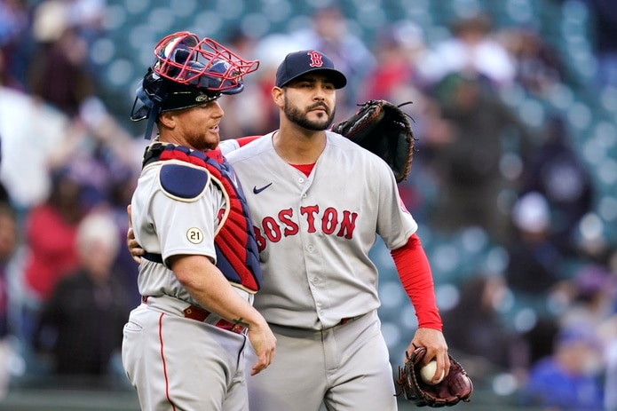 Boston Red Sox catcher Christian Vazquez, left, throws his arm around closing pitcher Martin Perez after the team beat the Seattle Mariners in a baseball game Wednesday, Sept. 15, 2021, in Seattle. The Red Sox won 9-4 in 10 innings. (AP Photo/Elaine Thompson)