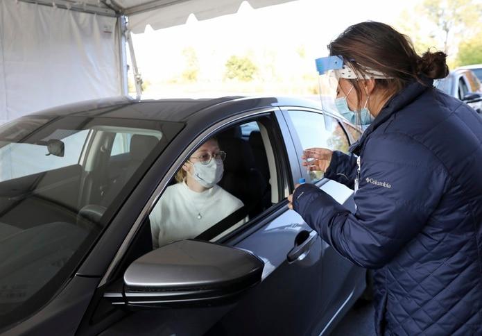 Una enfermera se presta a tomar una muestra por servicarro de la prueba molecular del coronavirus.