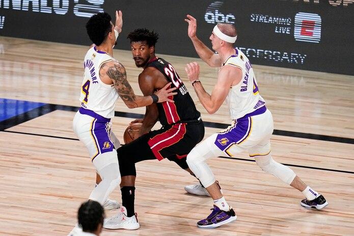 Jimmy Butler (al centro) del Heat de Miami, busca pasar contra Danny Green (14) y Alex Caruso (4), de los Lakers de Los Angeles, durante la primera mitad del Juego 6 de las Finales de la NBA.