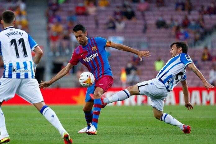 David Silva (derecha) de la Real Sociedad pugna un balón con Sergio Busquets del Barcelona en un partido de la Liga española, el domingo 15 de agosto de 2021. (AP Foto/Joan Monfort)