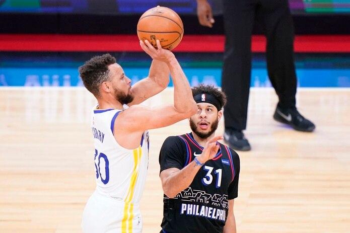 Stephen Curry, de los Warriors de Golden State, se levanta para tirar mientras lo observa su hermano Seth Curry, de los Sixers de Filadelfia.