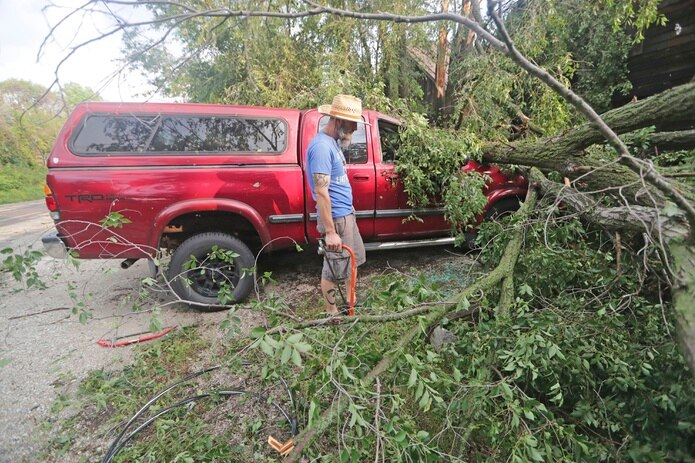 Adam Turley examina los daños sufridos por la camioneta de su padre delante de su casa en Concord Center Drive, en Concord, Wisconsin.