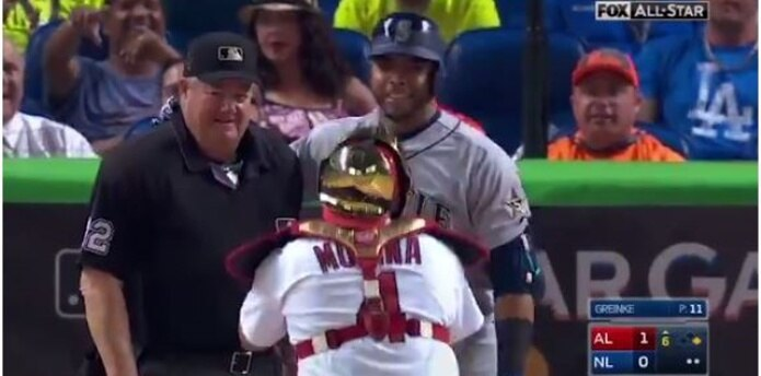 Yadier Molina acepta el sorprendente pedido de Nelson Cruz y le toma una foto junto al umpire Joe West. (Captura)