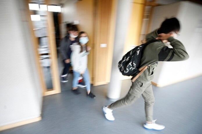 Alumnos con mascarilla salen de su escuela en Bischheim, a las afueras de Estrasburgo, Francia.