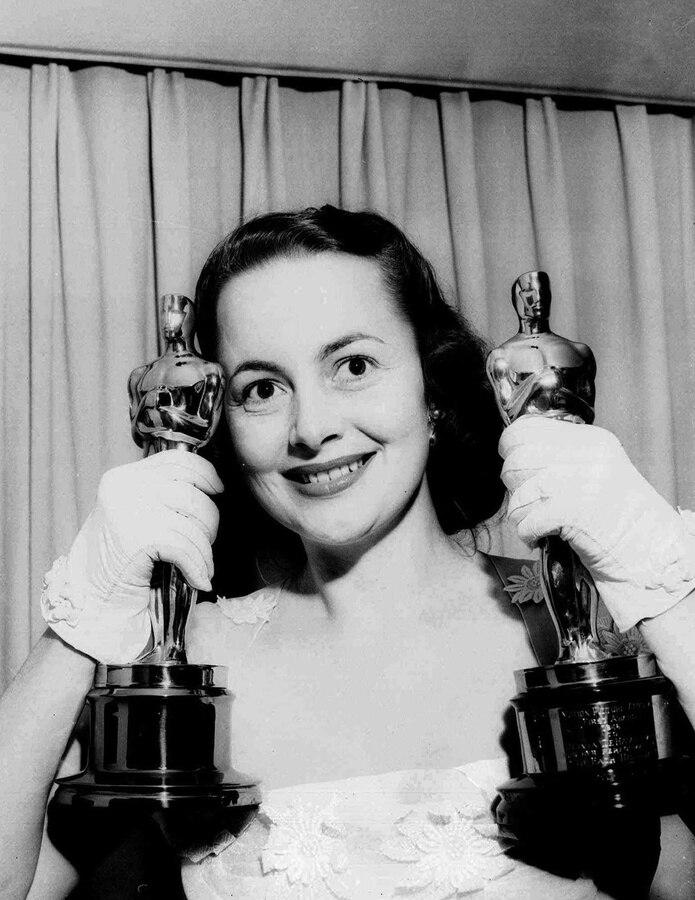 """Olivia de Havilland, en una foto tomada en su hogar en 1950 sosteniendo sus dos premios de la Academia de Artes y Ciencias Cinematográficas. Ese año ganó el Oscar por su actuación en """"The Heiress.""""  En 1946 había recibido su primera estatuilla por """"To Each His Own."""""""