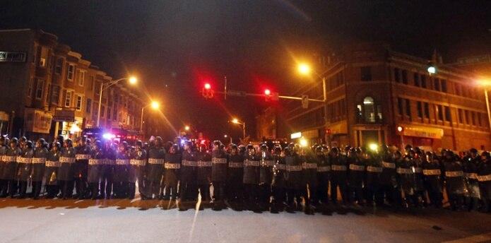 Policías de Baltimore prestaban vigilancia anoche durante el toque de queda ordenado tras los disturbios en esa ciudad. (Prensa Asociada)
