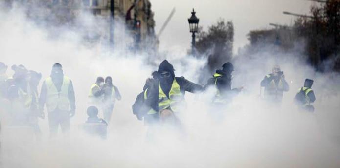 Manifestantes enmascarados protestaron el pasado sábado cerca de la avenida Champs-Elysees en París. (AP / Kamil Zihnioglu)