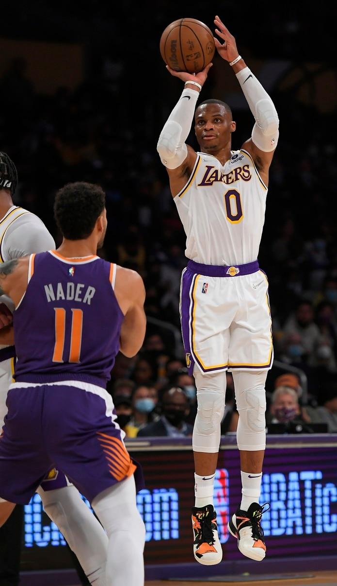El alero de los Suns de Phoenix Abdel Nader observa mientras el base de los Lakers de Los Ángeles Russell Westbrook lanza el balón en el encuentro de pretemporada. Los Lakers están listos para buscar un campeonato con un renovado roster lleno de jugadores experimentados.
