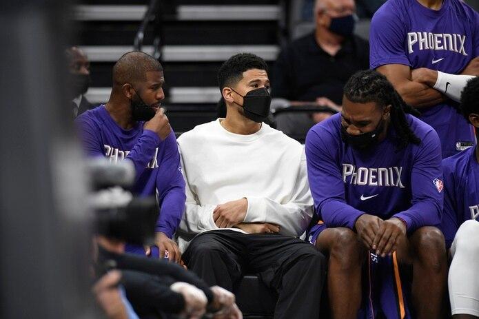De izquierda a derecha, Chris Paul, Devin Booker y Jae Crowder, de los Suns de Phoenix, conversan durante un partido de pretemporada en Sacramento, el lunes 4 de octubre de 2021.