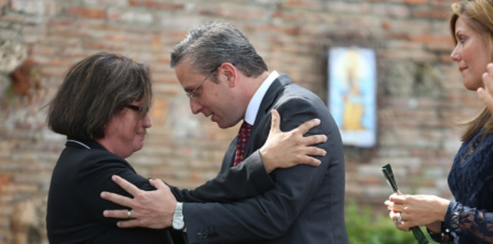 El gobernador abraza y parece tratar de consolar a la secretaria de Agricultura, Myrna Comas. Observa, la primera dama Wilma Pastrana. (VANESSA.SERRA@GFRMEDIA.COM)