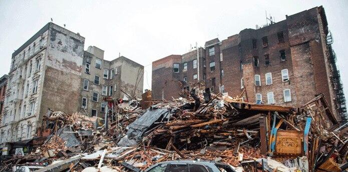 Bomberos trataban de extinguir ayer con fuertes chorros de agua las llamas en el lugar de una explosión en el barrio de East Village, en Manhattan, al tiempo que las autoridades reportaron que dos personas seguían desaparecidas. (AP)