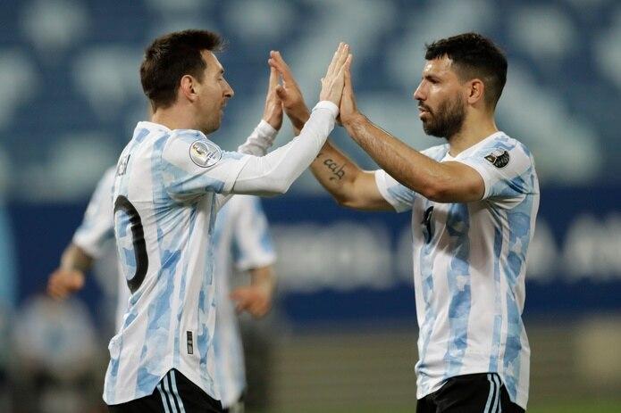Lionel Messi y Sergio Agüero chocan manos tras otro puntos en el desafío.