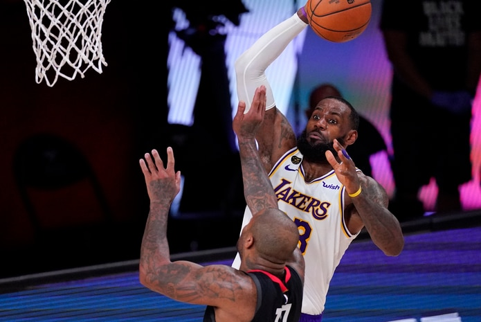 LeBron James, de los Lakers de Los Angeles, se dirige a colar un canasto sobre P.J. Tucker, de los Rockets, durante la acción del martes.