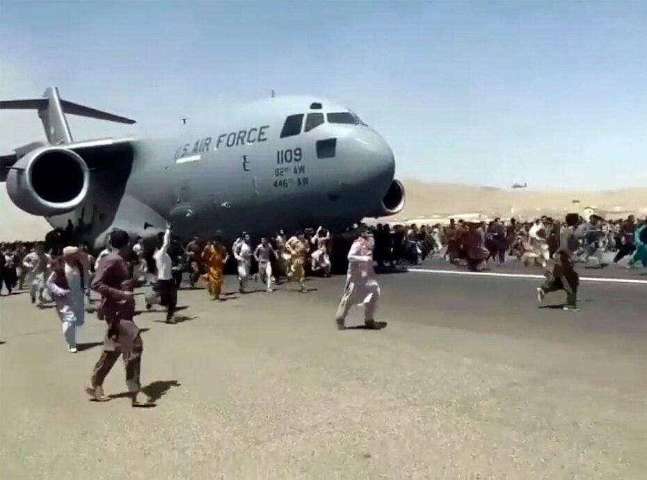 Cientos de personas corren junto a un avión C-17 de las fuerzas armadas de Estados Unidos en el aeropuerto de Kabul en Afganistán.