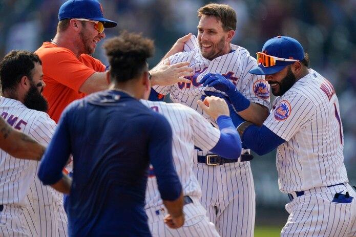 Jeff McNeil, segundo desde la derecha, es felicitado por sus compañeros de los Mets luego de conectar el hit que les dio la victoria el miércoles en el primer desafío de un doble juego.