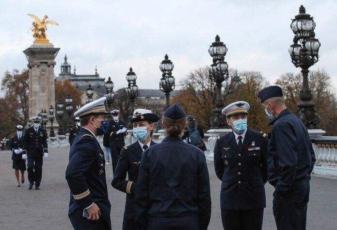 Efectivos del ejército francés usan mascarillas mientras se congregan en el puente Alexander III después de una ceremonia castrense en París.