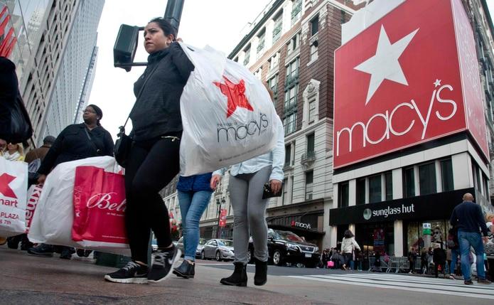 Clientes salen de la tienda de Macy's, en Herald Square, Nueva York. La ropa y calzado invernal son de los productos más afectados. (AP)