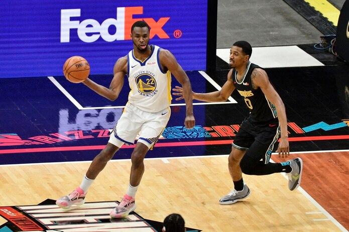 El alero de los Warriors de Golden State, Andrew Wiggins (22), maneja el balón contra el base de los Grizzlies de Memphis, De'Anthony Melton (0).