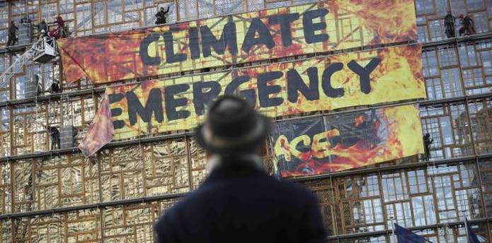 Un hombre observa una pancarta que denucia la inacción ante el cambio climático. (AP)