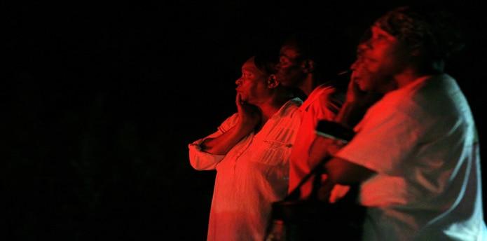Personas miran a lo lejos el fuego en la iglesia Mount Zion, una de siete iglesias incendiadas en las pasadas dos semanas. (AP)
