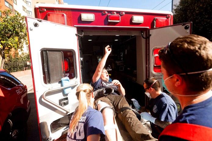 Un partidario del presidente Donald Trump que participaba en una manifestación con un reducido número de personas es subido a una ambulancia por paramédicos después de que contramanifestantes los agredieran en San Francisco.