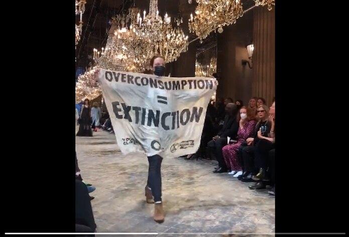 """La fémina protestó el consumo excesivo y caminó toda la pasarela con una pancarta de tela que leía """"consumo excesivo = extinción""""."""