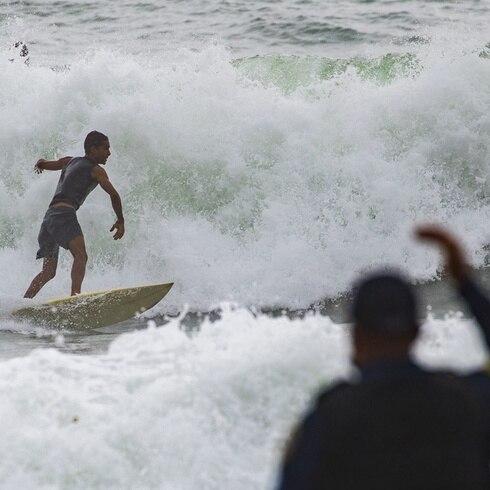 Surfers se tiran al mar en la playa Aviones en Loíza