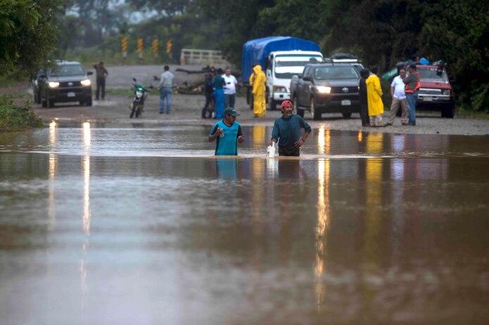 Dos hombres cruzan por un camino inundado en la comunidad Okonwas hoy, durante el paso del huracán Eta sobre la costa caribe norte en Rosita (Nicaragua).