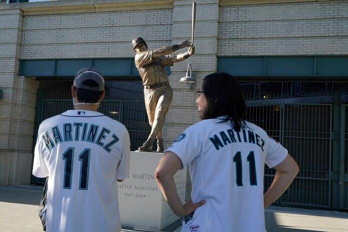 Dos fanáticos observan la estatua que ubica en las afueras del estadio en la calle que lleva el nombre del pelotero boricua.