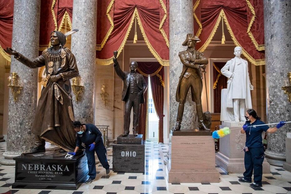 Empleados limpiaban los residuos de polvo de los pedestales de las estatuas en el Statuary Hall, en el interior del Capitolio.