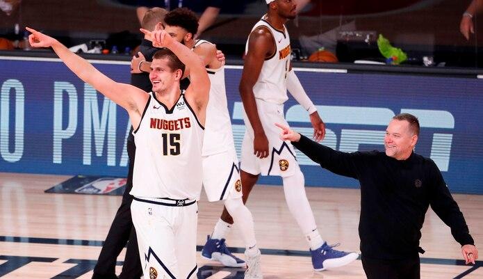 Nikola Jokic, de los Nuggets de Denver y el dirigente Michael Malone (derecha) celebran tras vencer y eliminar a los Clippers de Los Angeles.