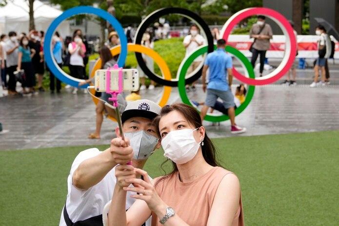 Una pareja se saca fotos afuera del Estadio Olímpico en la víspera del final de los Juegos Olímpicos de Tokio.
