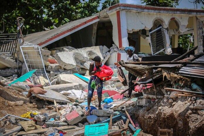 Unas mujeres recuperan sus pertenencias de sus casas destrozadas el domingo 15 de agosto de 2021, en Les Cayes, Haití, luego de un sismo de magnitud 7,2. (AP Foto/Joseph Odelyn)