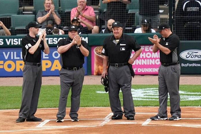 El árbitro Joe West, segundo desde la derecha, recibe aplausos de sus colegas mientras en la pantalla del estadio se mostraba aun vídeo sobre su carrera. Los oficiales que le acompañaban son, de izquierda a derecha, Nic Lentz, Bruce Dreckman y Dan Bellino. En cuanto a público presente, este mayormente le abucheo durante el reconocimiento.