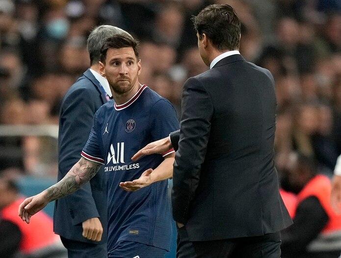 Lionel Messi observa al técnico el PSG Mauricio Pochettino tras ser sustituido en el partido contra Lyon por la liga de Francia.