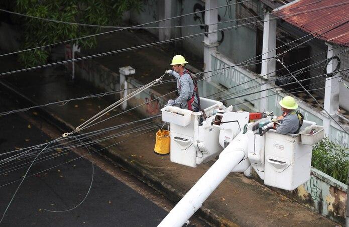 Una brigada de la Autoridad de Energía Eléctrica trabaja en la calle del Parque en Santurce luego del paso de la tormenta Isaias.