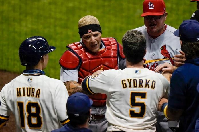 Yadier Molina discute con Keston Hiura y Jedd Gyorko, de los Brewers, en la quinta entrada.