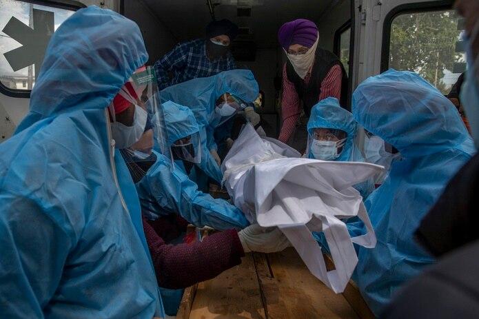 Voluntarios retiran el cuerpo de un muerto por COVID-19 del interior de una ambulancia para cremarlo.