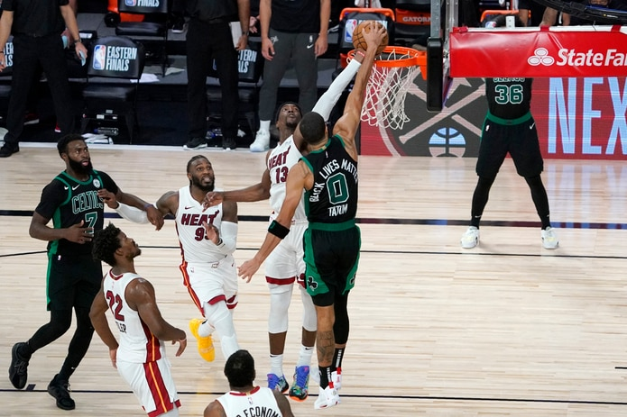 Bam Adebayo (13) le da un tapón a Jayson Tatum en un intento de donqueo para finalizar el tiempo extra a favor del Heat.