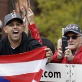 Alex Cora no suelta su bandera durante la parada de celebración de los Medias Rojas en Boston