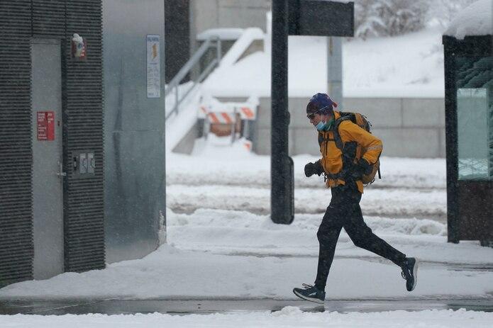 Una persona corre en medio de la tormenta de nieve en el campus de la Universidad de Washington en Seattle.