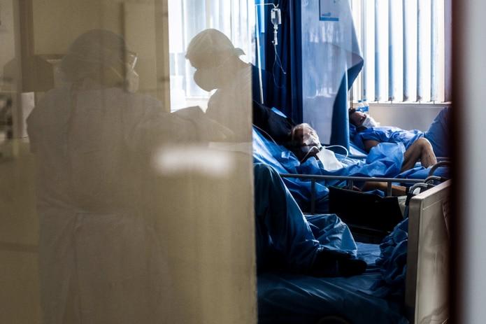 Trabajadores de la salud atienden a un paciente contagiado con coronavirus.